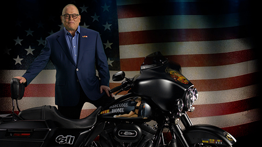 Bob Parsons next to a motorcycle, in front of a flag